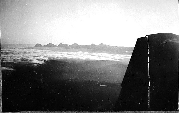 Luftfoto, fjell og skydekke under. Litt av ene vingen på flyet bildet er tatt fra, Junkers, sees.