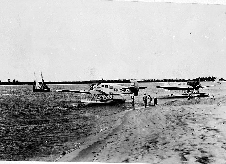 """2 fly på bakken ved vannkanten. Junkers Ju-34. Flyet foran PP-CAP """"Taquary., bak Ta...?. Begge fra Brazil. 1 seilbåt ute på havet."""