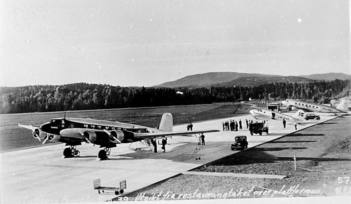 Lufthavn. Flere fly parkert på rekke. Flere personer. Det nærmeste Focke Wulf Condor