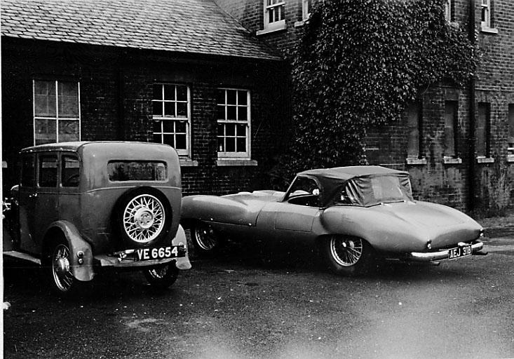 2 kjøretøy, personbiler, parkert foran større bygning. En av bilene er en sportsbil.
