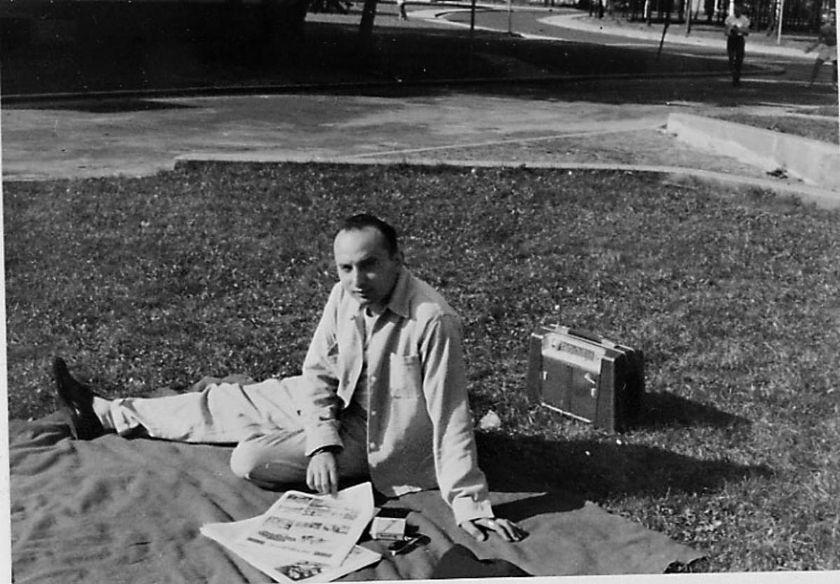 Portrett, 1 person sitter i en park e.l. med en kombiradio ved siden av.
