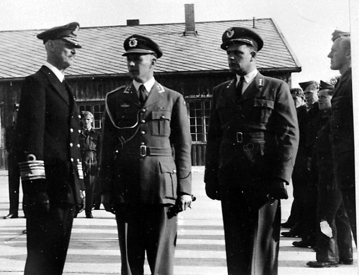 Portrett, 3 personer, i militæruniform, i forgrunnen. Soldater oppstilt bak. Kong Haakon t.v.