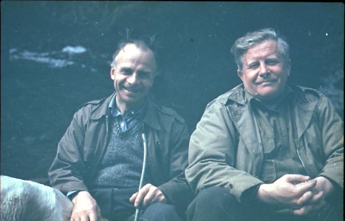 Portrett, 2 persone sitter og slapper av ute i terrenget. Ryggen på en hund seet nede t.v.