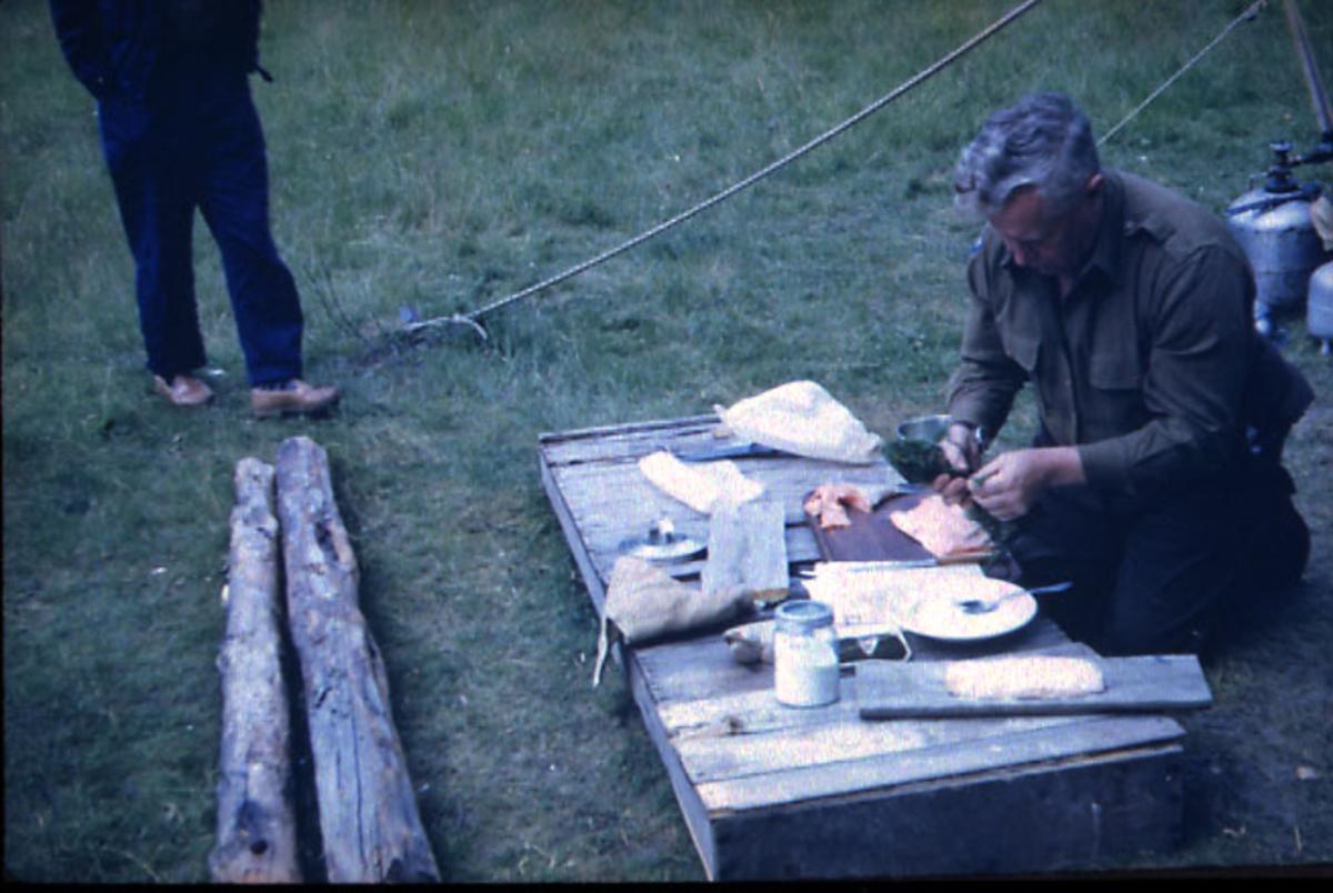 Portrett, 1 person sitter ved en benk/kasse utendørs og tilbereder fisk - laks. Føttene på 1 person sees oppe i billedkanten.