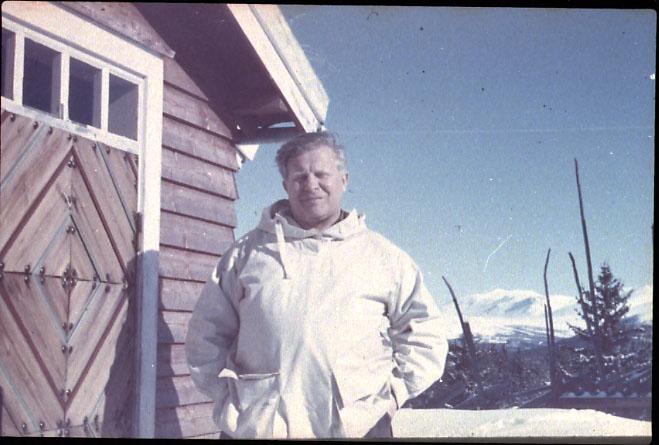 Portrett, 1 person i hvit anorakk, brystbilde, tatt utewndørs. Bygning t.v. Snø på bakken