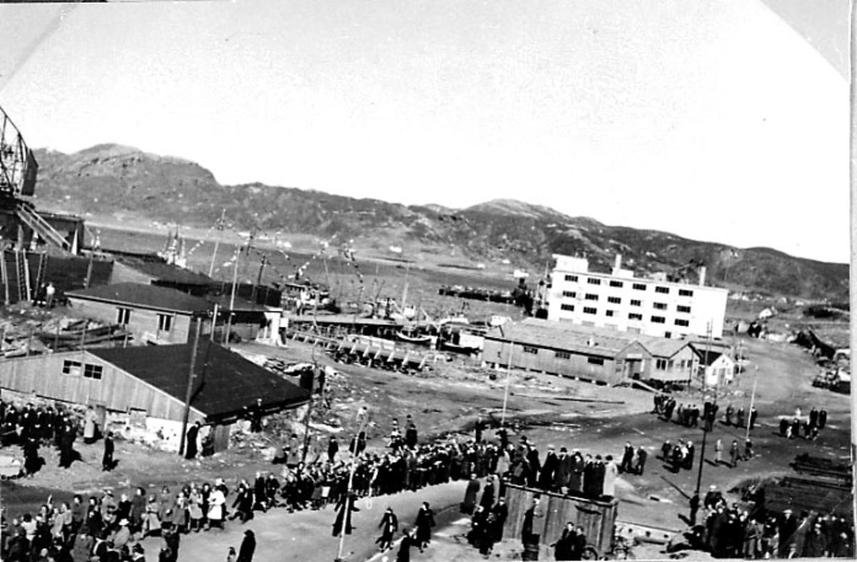 By, oversiktsfoto. Stor folkemengde i gatene. Noen bygninger - brakker. Havneområde i bakgrunnen.