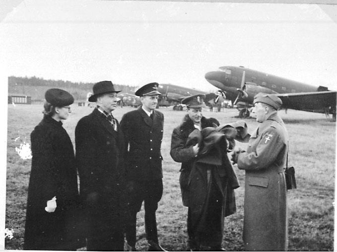 Lufthavn, portrett av 5 personer (noen i militæruniform). Bak står 2 fly parkert på bakken. Tatt utendørs.