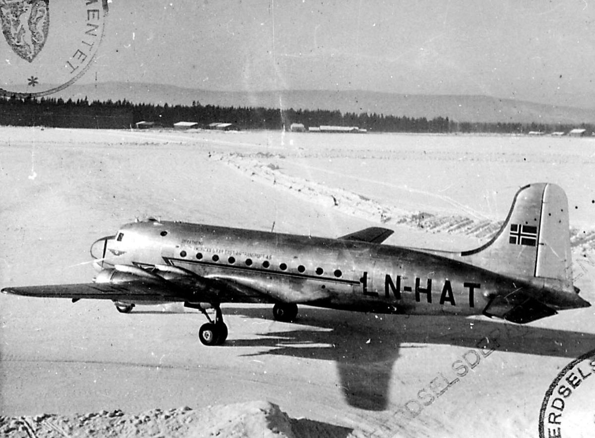 """1 fly på bakken, Douglas DC-4 /C-54A, LN-HAT """"Norse Skyfarer"""" fra Braathens SAFE A/S. Flere bygninger i bakgrunnen."""