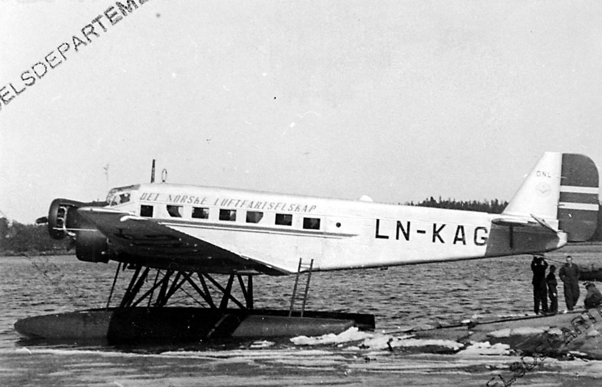 "1 fly, Junkers JU 52 3mg7e, LN-KAG ""Veslefrikk"" fra DNL A/S Oslo, ligger stille på havoverflata, ved land. Flere personer ved halepartiet."