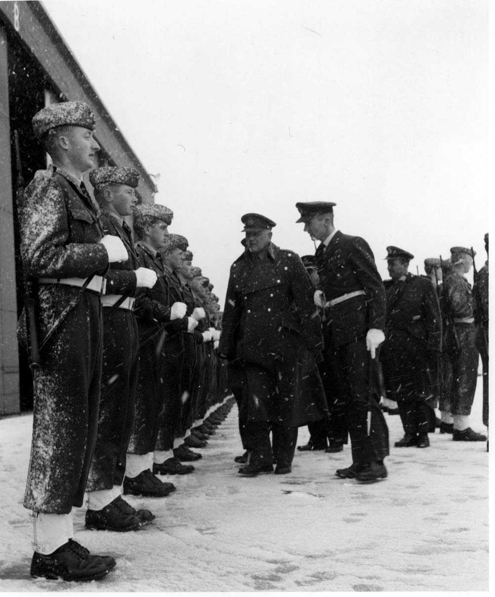 Gruppe   Inspeksjon av oppstilt  miltært personell i snøvær.
