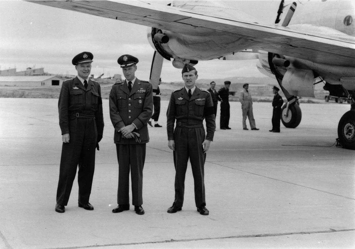 Gruppe  Tre personer i uniform ved siden av et fly.