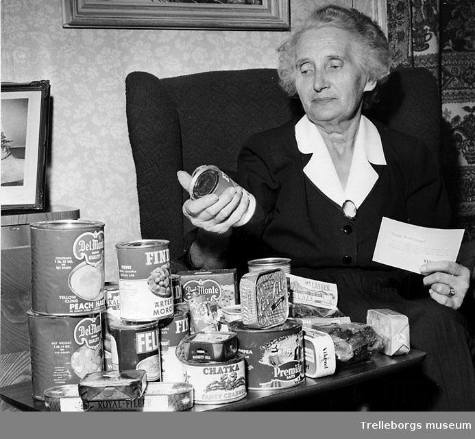 Ruth Jönsson med ett litet berg av konservburkar som Kvällsposten har förärat henne. Kanske har hon vunnit en tävling?
