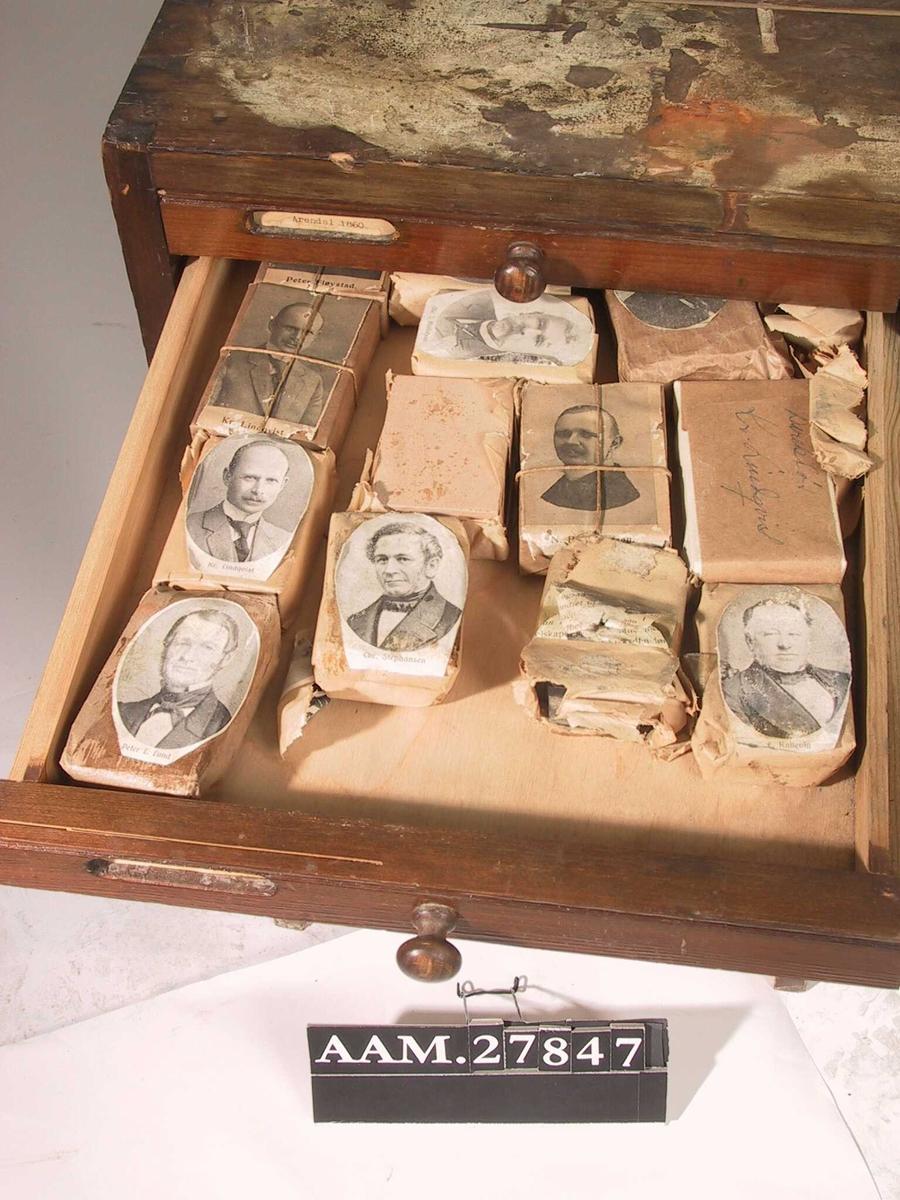 Rektangulært skap med 16 lave skuffer tilpasset klisjetykkelse. Inneholder klisjer fra en lang tidsperiode, brukt til forskjellige trykksaker fra Arendals Forsikringsselskab. Noen av skuffene har etiketter i forkant: Arendal 1860 / Direksjonen 1860 - 1920 / Navn og annonser / Arendal 1920 // Kjetting / Bilpoliser / Merker / Jubileumsklisjeer / Tegninger og fotografier  I en av skuffene  ligger en brosjyre på klisjeskap fra firma Jens Aanessen, Oslo.