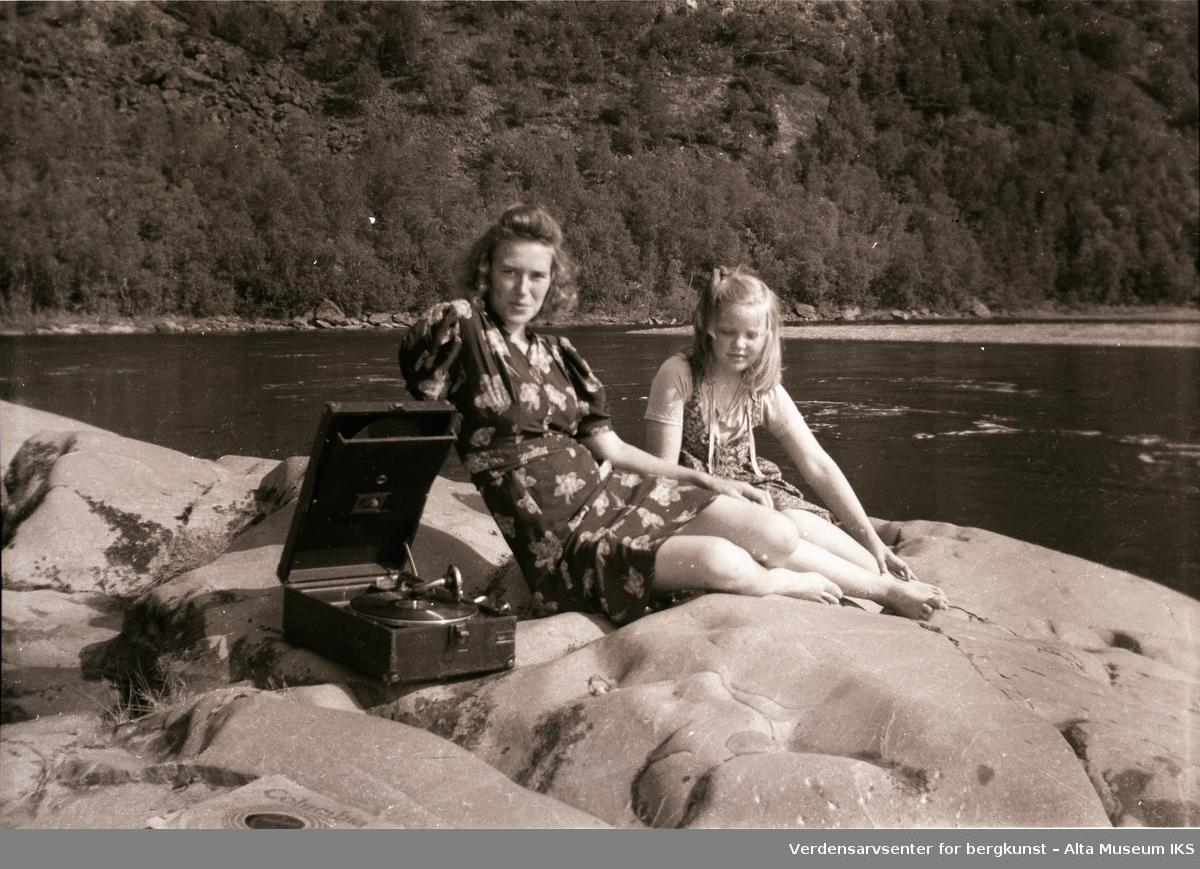 Erna Jøraholmen og Britt Myreng slapper av på berget ved elvebredden, Jorra, sent på 1940-tallet. Grammofonen sørger for god stemning.