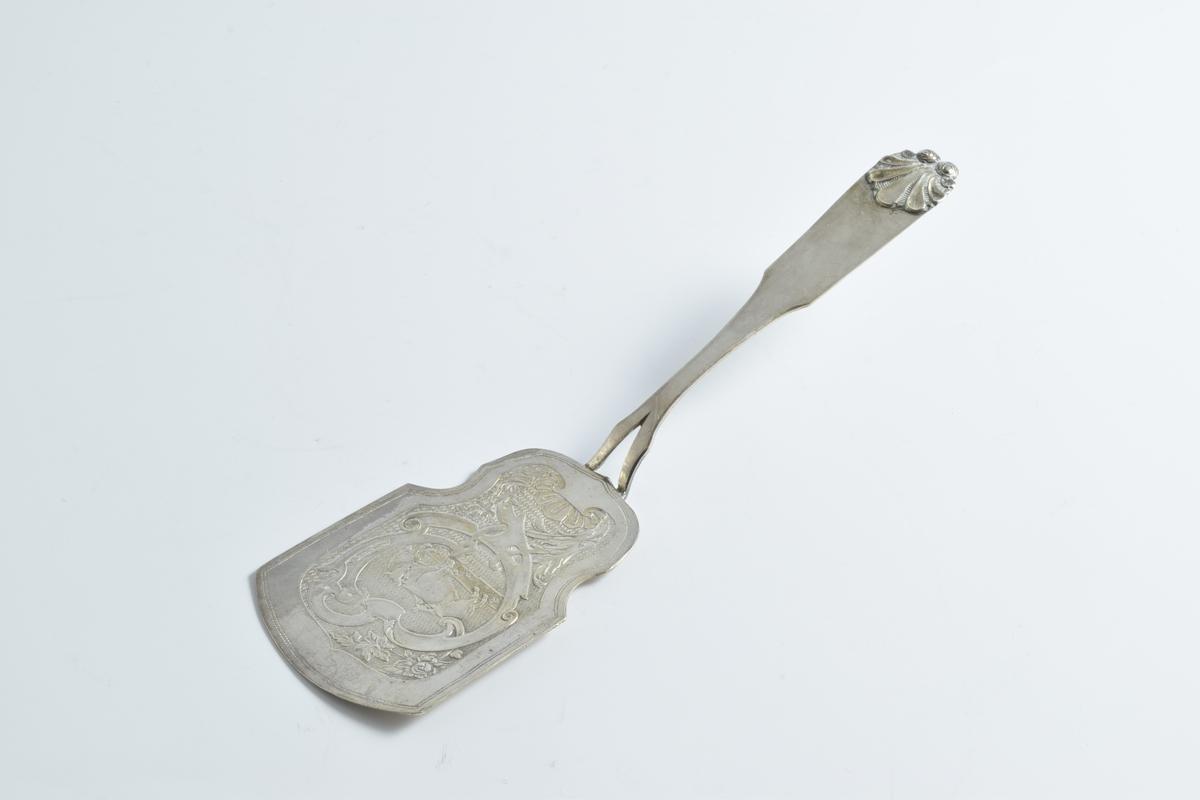 Eggespade av sølv. Bladet har en småriflet bunn med motiv av en ku og en okse i en ramme av fliket båndornament og blomster. Den øverste delen av skaftet er prydet med et støpt skjell.