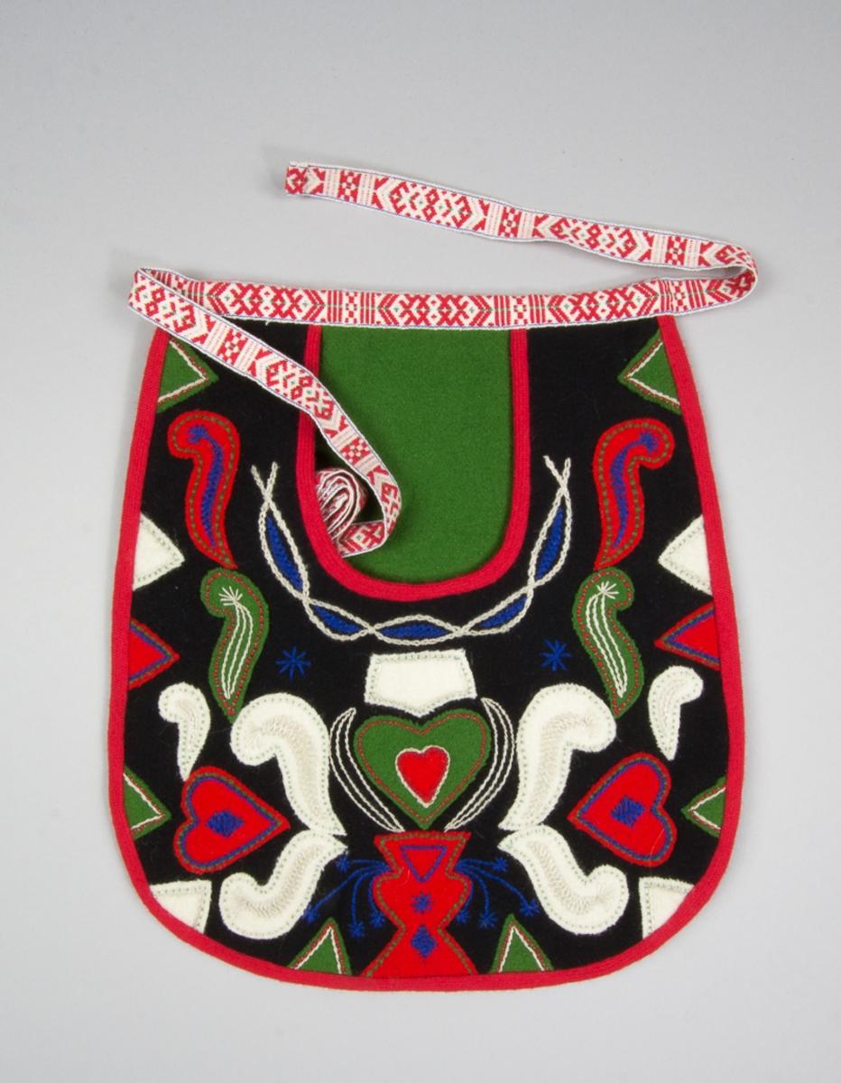Kjolsäck till dräkt för kvinna från Leksands socken, Dalarna. Modell med u-formad öppning. Framstycke av svart ylletyg, kläde, med applikationer av kläde i vitt, rött och grönt, fastsydda med läggsöm. Motiv: urna med uppstående hjärtan och slingor, trekanter på sidorna. Broderi utfört med bomullsgarn i flera färger: stjälksöm, flätsöm och sticksöm. Foder av grön konstsidentaft. Kantat runtom med rött diagonalvävt ylleband. Spegel av grönt kläde. Bakstycke av svart kläde. Midjeband troligen handvävt, med plockat mönster med rött ullgarn på vit botten.