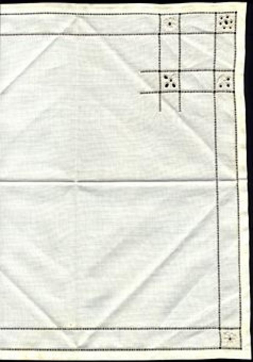 """Åtta stycken likadana servetter i linne med vitbroderi. Innanför fållen löper två hålsömsrader med 15 mm mellanrum. I hörnen där linjerna möts bildas en ruta, i denna är en blomma broderad; alla olika. I ett av hörnen bildar fler hålsömsrader ett större kvadratiskt mönster med ytterligare tre rutor; alla med en blomma i. Blommorna är broderade i klumpsöm eller fylld dubbelsidig plattsöm och hål kantade med kastsöm. Varje servett är vikt tre gånger och ligger i en bunt omknuten med ett lila konstsidenband vari sitter ett fastknutet kort med handskriven text: """"Malmö Husläns Hemslöjd"""". Tillhörande duk; se inv. nr 874."""