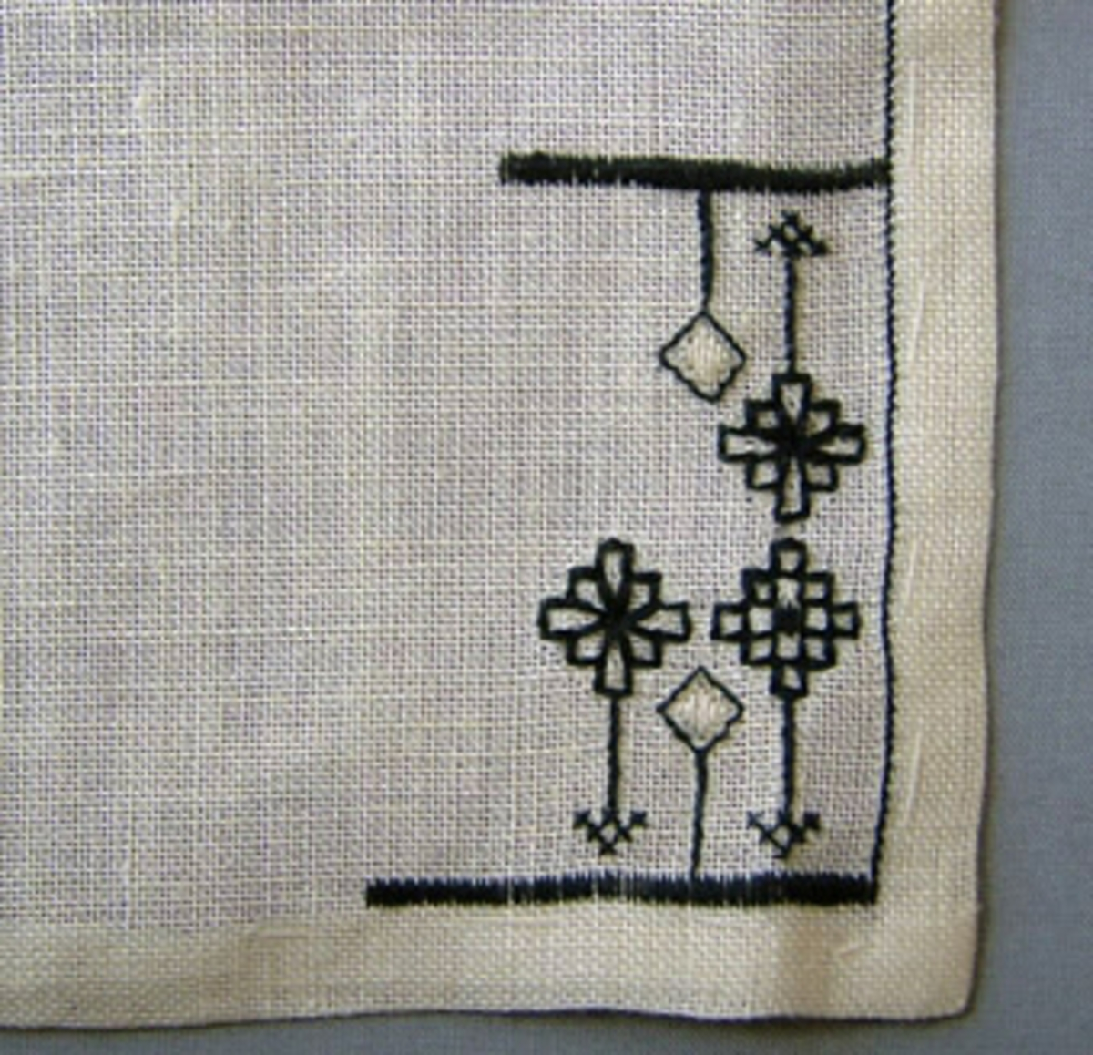 Broderiprov i linne med broderi i svartstick. Broderiet är påbörjat i ena hörnet av den fållade linneväven. Motivet, stiliserade blommor och svarta ränder, är utfört i rätlinjig plattsöm, korsstygn och rutsöm. Blekt/vit linneväv med broderi i svart och lite vitt.