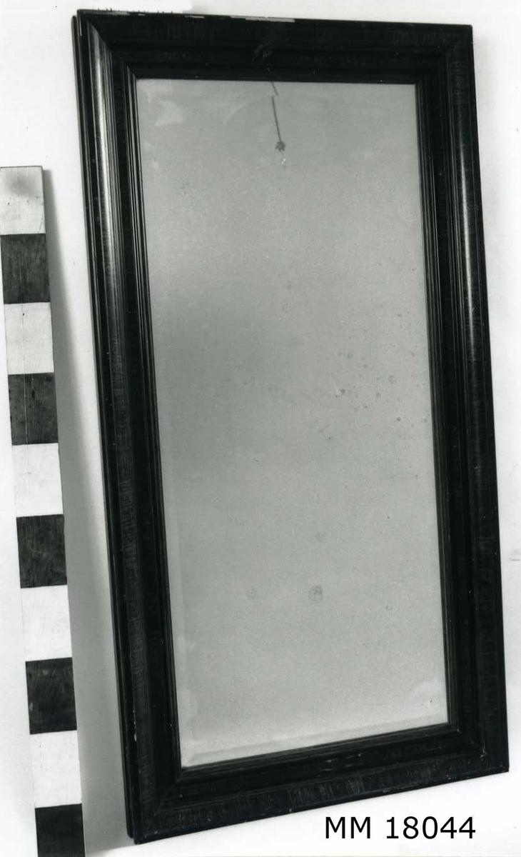 """Rektangulär spegel med slipat glas, profilerad ram, imitationsmålad i trä, B = 100 mm. Baksida klädd med kartong. Skrivet för hand: """" Örlogshemmet """". Öglor och snöre för upphängning."""