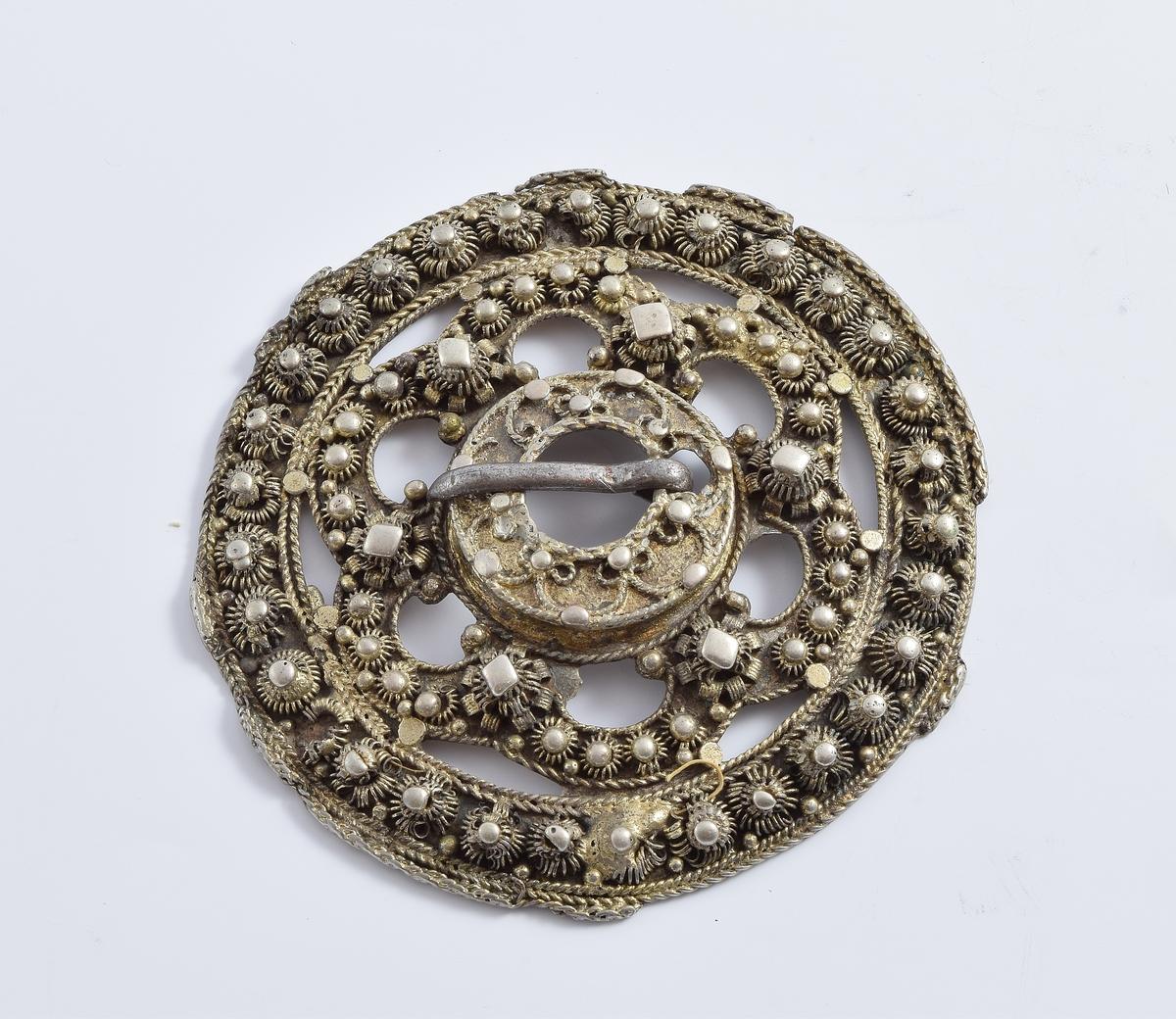 Slangesølje av forgylt sølv med kruseperler. Ringen om tornhullet er opphøyet og har 7 pålagte trådbuer.