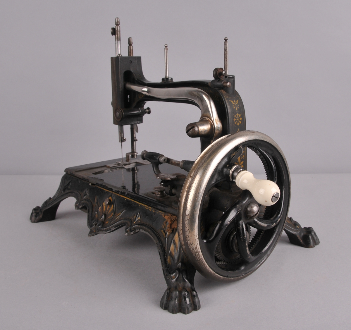 Symaskin i jern som står på fire løvefotforma bein. Sveiv med poselensknott.
