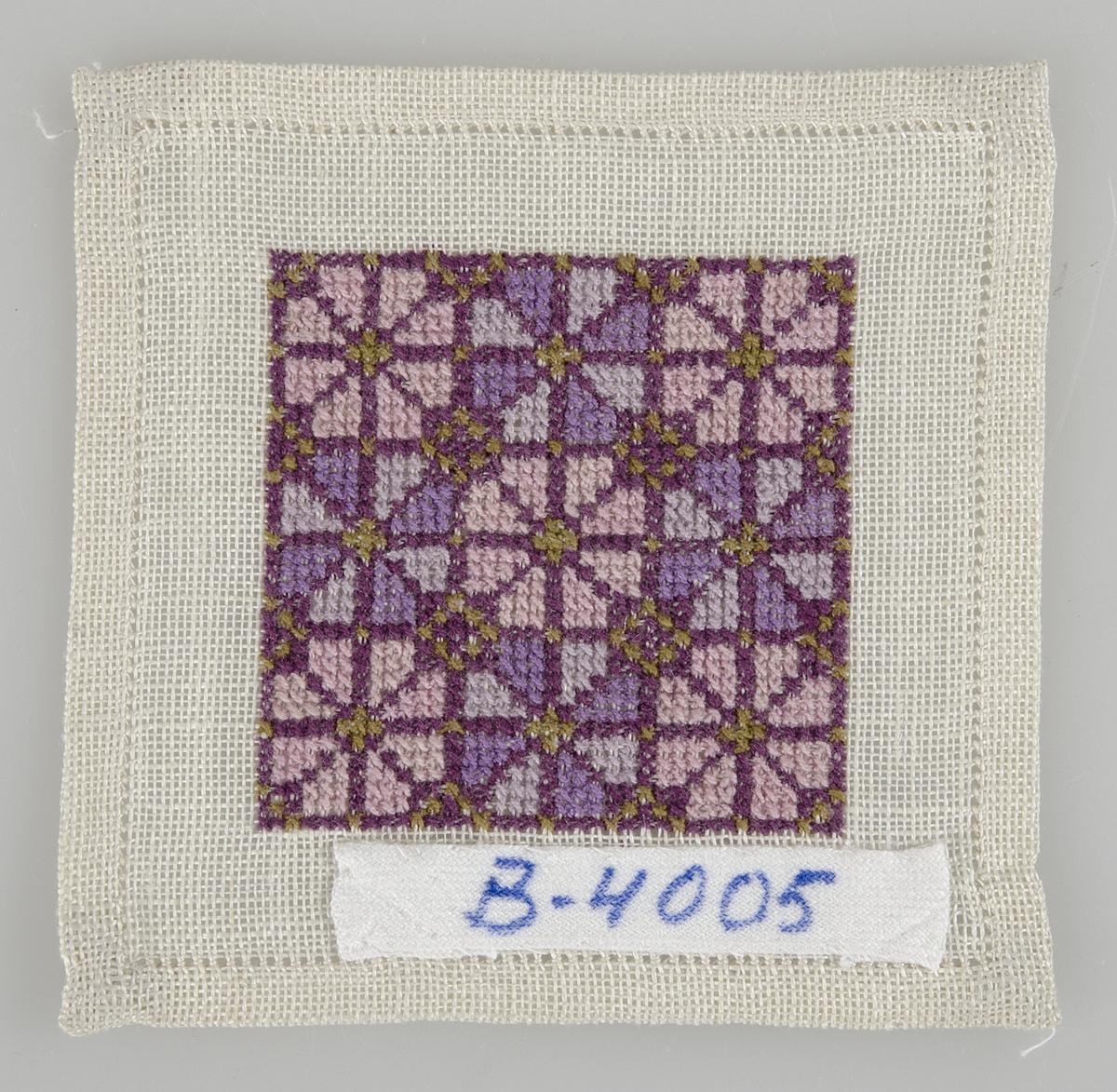 """Liten duk/mellanlägg med motivet i lila, rosa och gröna korsstygn. Duken är broderad med bomullsgarn på tyg vävt i tuskaft av lin. Duken/mellanlägget är märkt """"B-4005""""."""