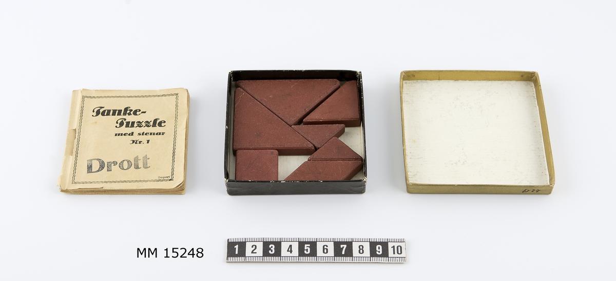 Tankepuzzle i en ask innehållande häfte och 7 stenar. Ask, kvadratisk papp-ask med svart låda och guldfärgat lock. Kvadratiskt häfte samt rödbruna olikformade stenar