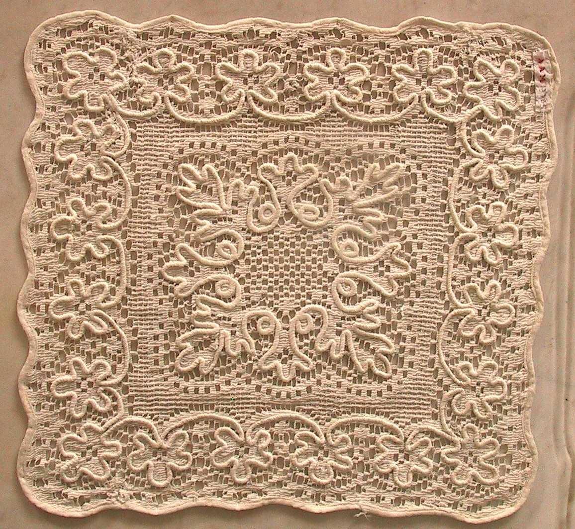 Liten firkantet brikke med hvitt kantebånd, bord av fembladede blomster langs kantene, spissbladet bord pm.   Filert, maskinlaget.  Tilstand: God