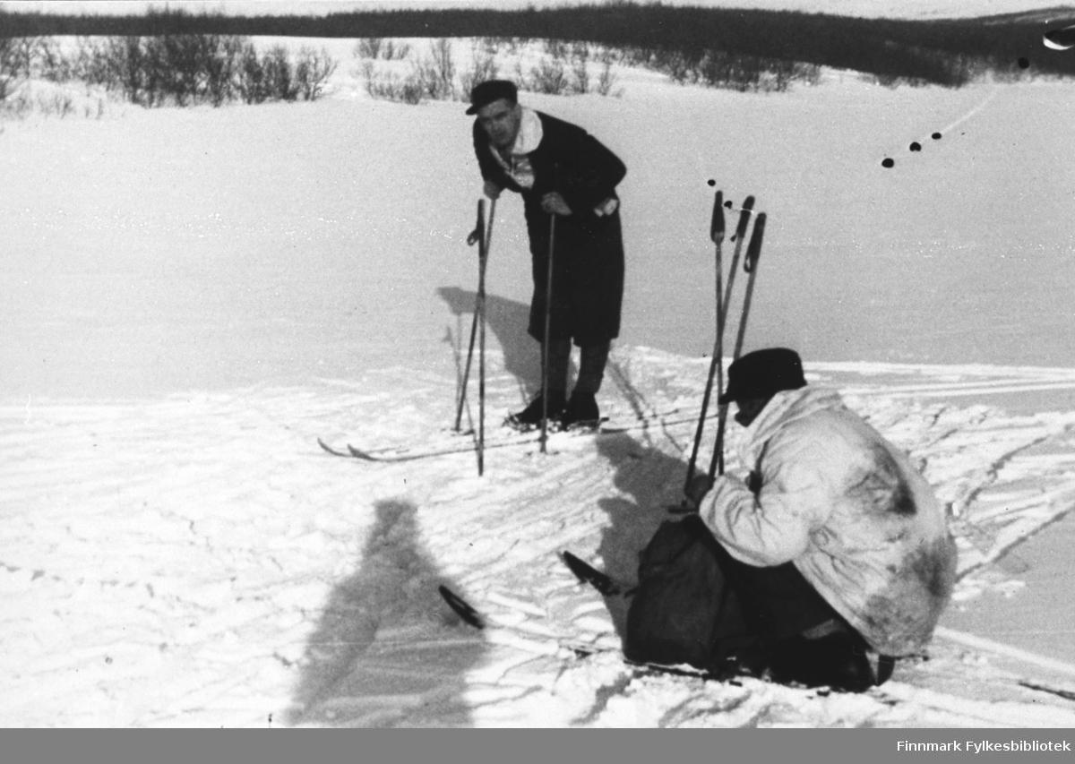 To menn går på ski på fjellet ovenfor Vestre Jakobselv. Den ene kneler og tar noen ut eller putter noen inn i ryggsekken sin. Den andre står ved sidan av han og lener mot stavan sine. Dagen er solig.