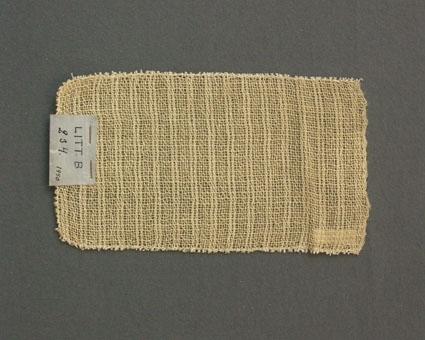 Prov till gardin vävd i tuskaft med glesa och tätare ränder. Provet har ullgarn i varp och inslag.Ytterligare prov och vissa vävuppgifter finns i pärm gardiner A, litt B 234.
