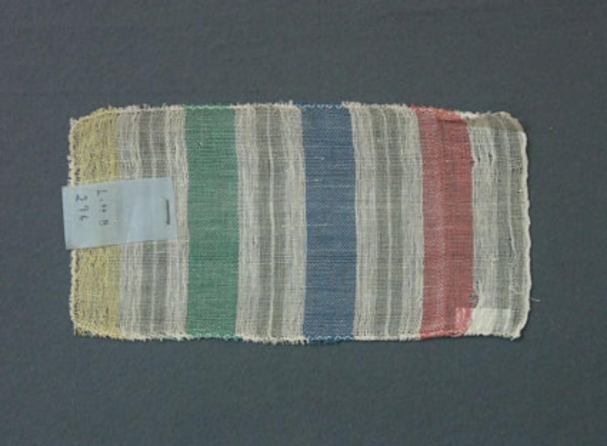 Prov till gardin vävd i tuskaft. Provet har bomullsgarn i varp och inslag.Ytterligare prov och vissa vävuppgifter finns i pärm gardiner B, litt B 296.