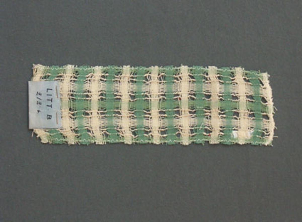 Prov till gardin vävd i tuskaft med hål, provet har bomullsgarn i varp och inslag.Ytterligare prov och vissa vävuppgifter finns i pärm gardiner A, litt B 212 b.