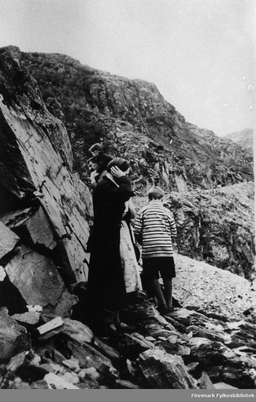 Fjellskjæringen utenfor Sjursjok. Her ser vi Fixdal med minste barnet på skuldrene etter ham går en annen av hans sønner og til sist en kvinne. De går langs skjæringen i fjellet.
