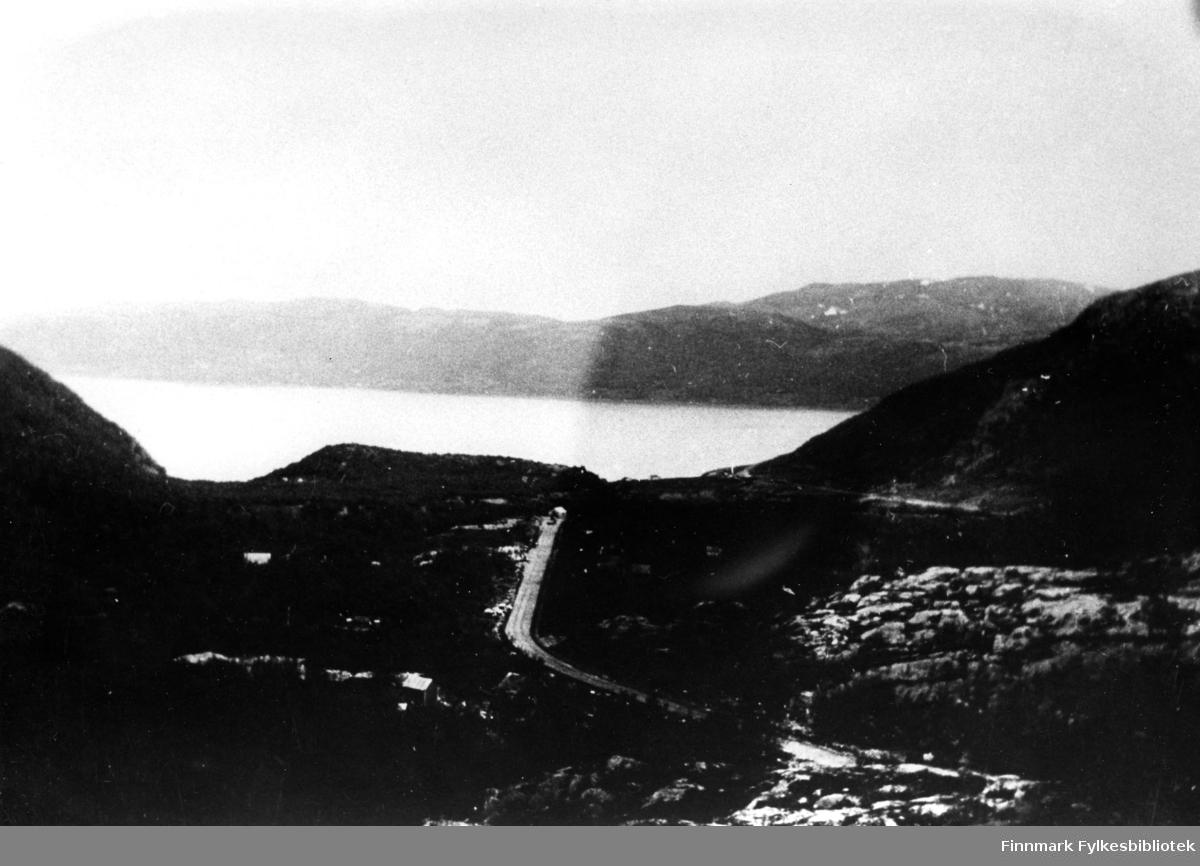 Oversiktsbilde av veien i Sjursjok i Tana. I midten ser man veien, til venstre brakkeleiren, i bakgrunnen en elv og noen fjell.