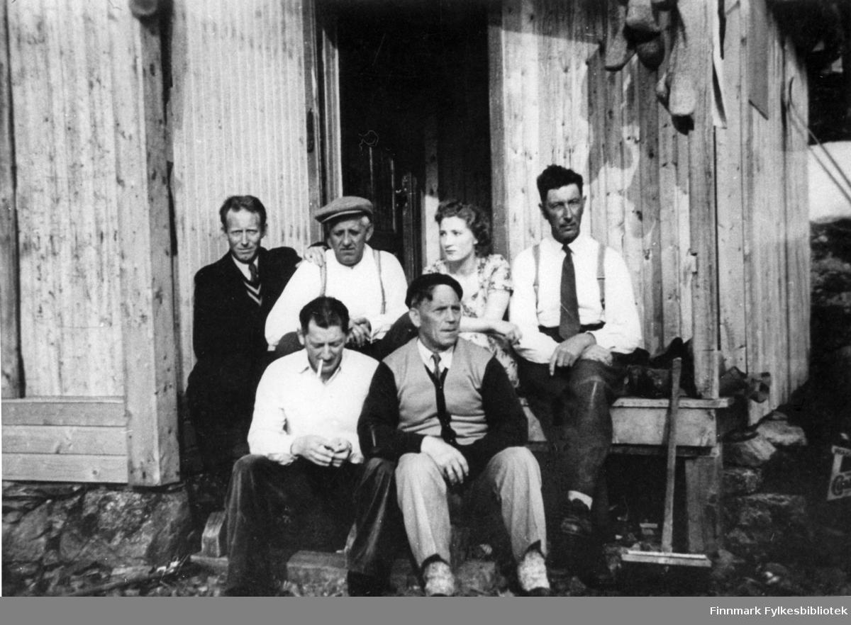 Portrettfotografi av en gruppe som sitter på trappa til en brakke. Forran fra venstre: Odin Nilsen og Håkon Iversen. Bak fra venstre: Agnar Iversen, Håkon Rapp, Sigrid Andersen og Odin Emaus.