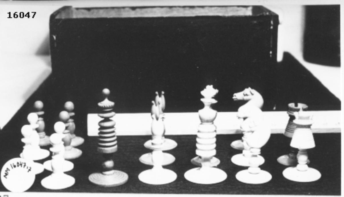 Utskuren schackpjäs, röd löpare, som står på cirkelrund fot.