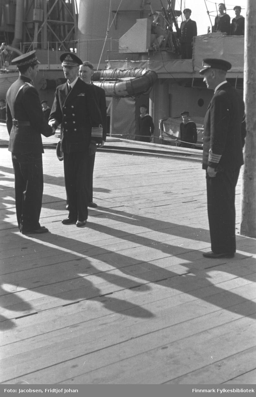Kongebesøket i Hammerfest 10. juli. Kong Haakon 7 hilser på politimester Arvid Dahl, sannsynligvis på Gabrielsen-kaia. To andre menn står på kaia, en i uniform og en i mørk dress. KNM Stord ligger ved kai og mannskap står i giv akt.