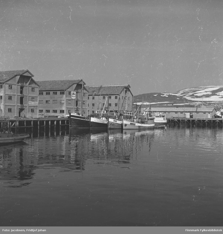 En vårdag i Hammerfest havn. De to byggene til venstre på bildet er pakkhusene til Trygve Nissen. Bygget ved siden av dem, midt på bildet, er Televerkets lager, Hammerfest folkebibliotek i dag. Den avlange brakka som står på kai til høyre på bildet er kailagret til FFR. Flere skøyter ligger fortøyd ved Nissen-kaia og hekken på en annen båt ses helt til venstre på bildet. Sykehuset kan ses rett over taket på FFR-brakka. Fjellet i bakgrunnen er Vardfjell med Storfjellet til høyre. En del snø ligger i fjellet enda som som vinter om en fin vårdag.