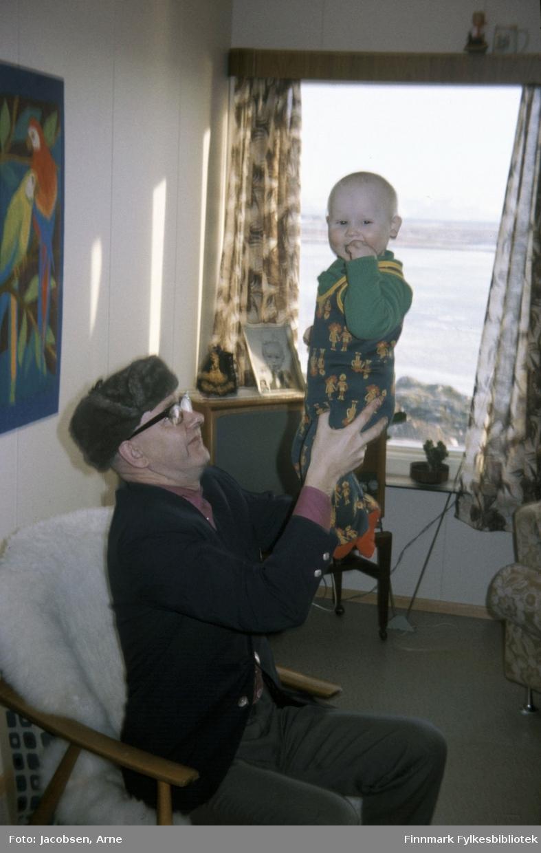 Morfar Peder Flatmo holder barnebarnet Tor Jørgen Jacobsen. Peder sitter i en lenestol med saueskinn og har en mørk dressjakke, dressbukse, skjorte og en skinnlue på hodet. Tor Jørgen har en buksedress med påtrykte figurer, seler og genser på seg. Bak de henger et bilde med fugler og delvis skult står et TV-apparat i hjørnet foran vinduet. Et innrammet barnebilde og en dukke er plassert oppå TV'en. Mønstrete gardiner under et gardinbrett med en figur oppå. Til høyre ses en liten del av en lenestol.