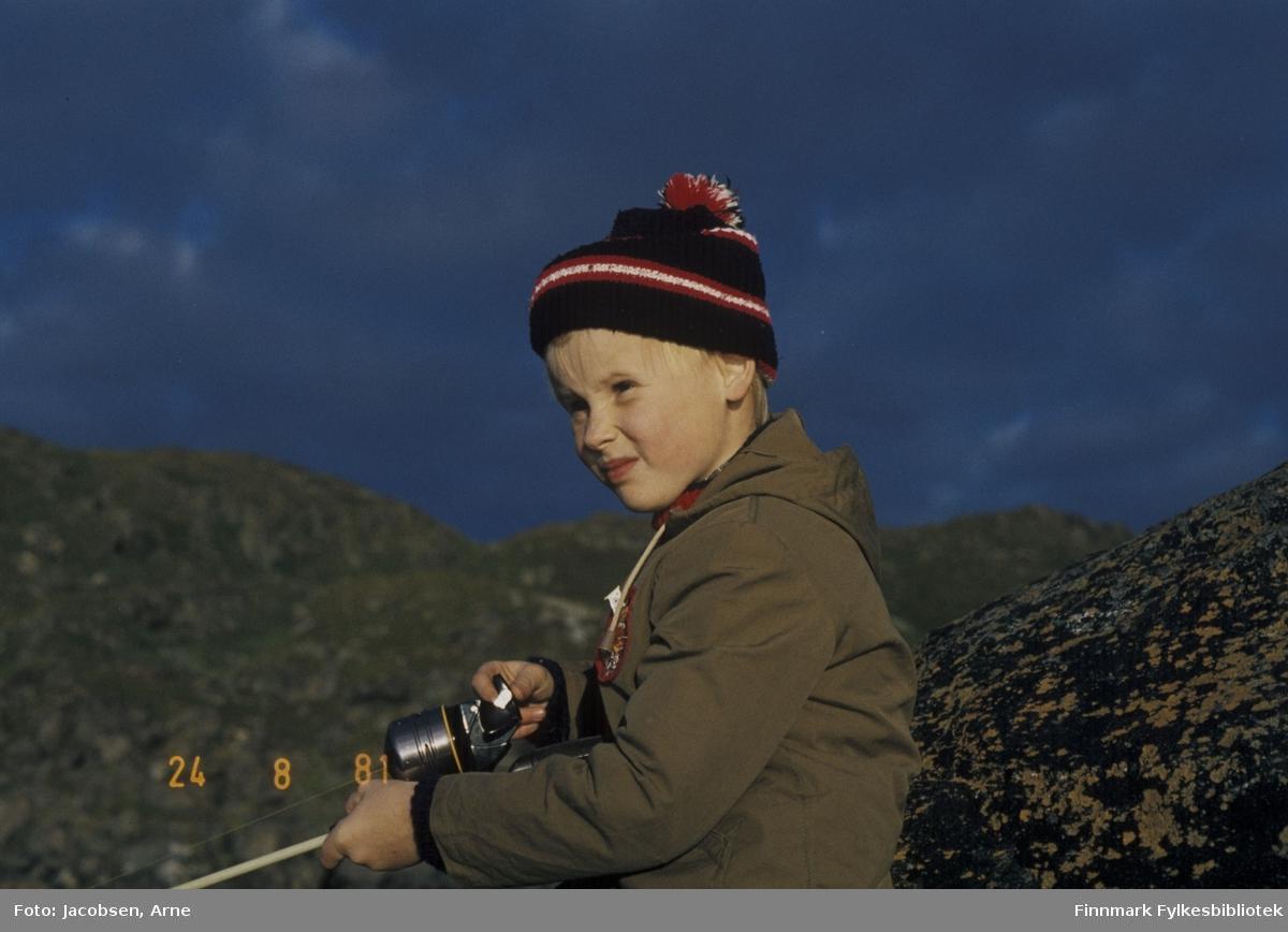 Tor Jørgen Jacobsen på tur med fiskestang. Han har topplue med dusk og hettejakke på seg mens han sveiver på en lukket haspelsnelle. Han sitter inntil et berg/en stor stein. Solen skinner, men skyet i bakgrunnen.