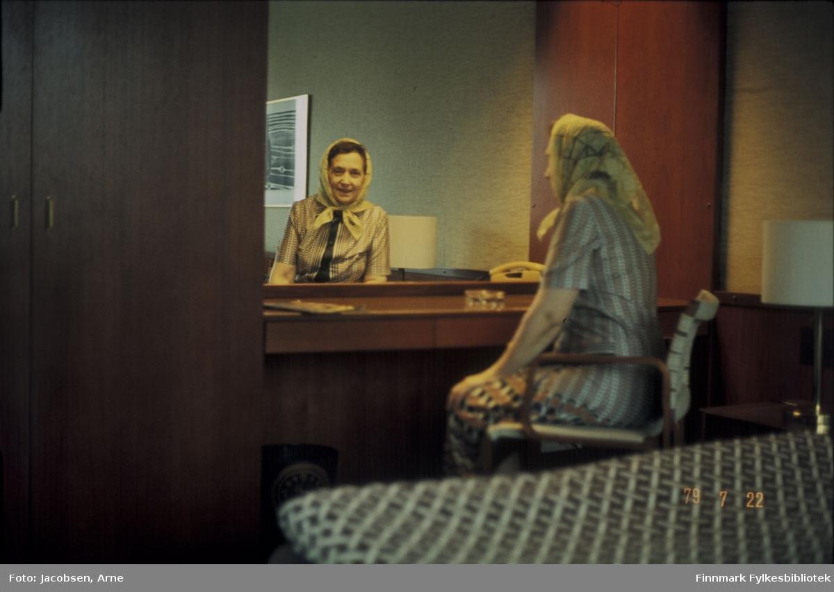 Aase Jacobsen på hotell. Hun sitter i en enkel stol foran et stort speil. Ryggen/siden mot fotografen - ansiktet som refleksjon i speilet. Hun har tørkle på hodet som er knytt i halsen, mønstret skjørt og stripet skjorte på seg. På bordet foran henne står et askebeger og en telefon. Til høyre er en lampe og til venstre et klesskap. Rutet/mønstret sengeteppe foran på bildet. I speilet ses også et bilde som henger på veggen bak henne.