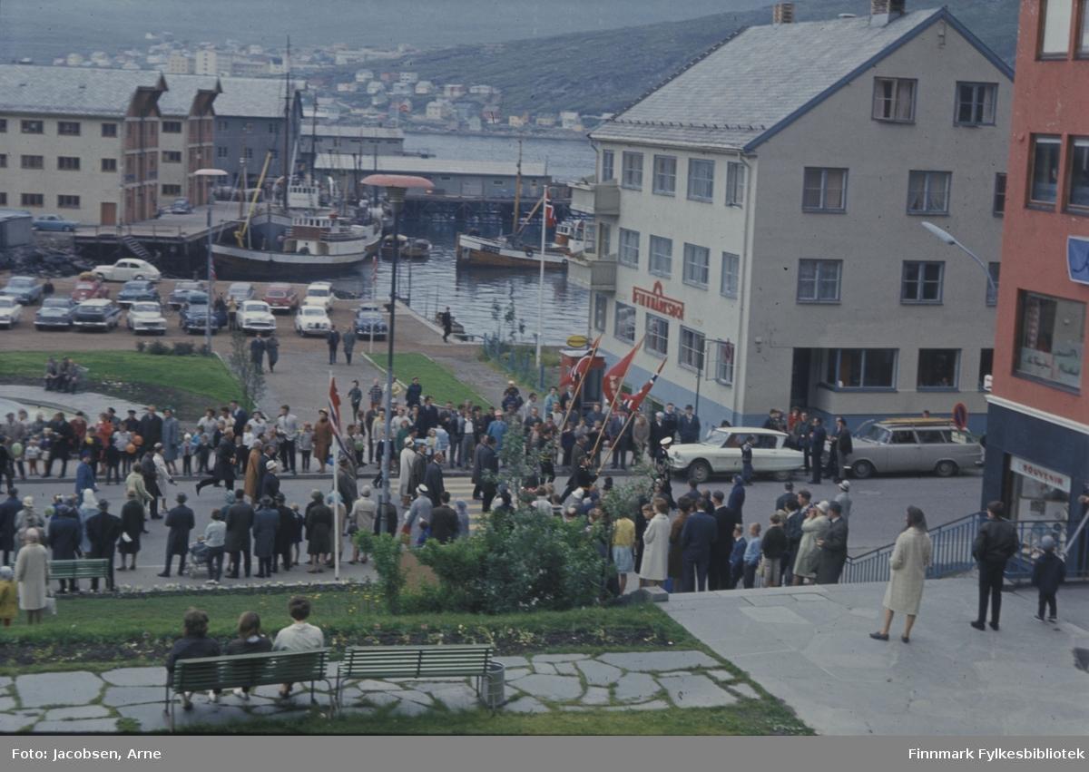 En markering i Hammerfest. Mye folk er oppstilt langs Strandgata og noen sitter på benken i parken/Ole Olsens plass. Endel står også i trappa fra parken og ned til Strandgata. På rådhusplassen er det stort sett parkerte biler og lite folk. I havna ligger noen fiskebåter ved Nissenkaia. Bygget til høyre er Finnmarksbo. Et par biler står parkert utenfor. En pen, hellebelagt sti går tvers over plenen nærmest hvor det også er satt ut benker som tre mennesker sitter på. Det norske flagg vaier fra flaggstenger og de fremst i toget har også flagg i hendene. Noe diffust i bakgrunnen ses deler av Fuglenes med sykehuset rett over taket på Televerksbygget og Nissengården.