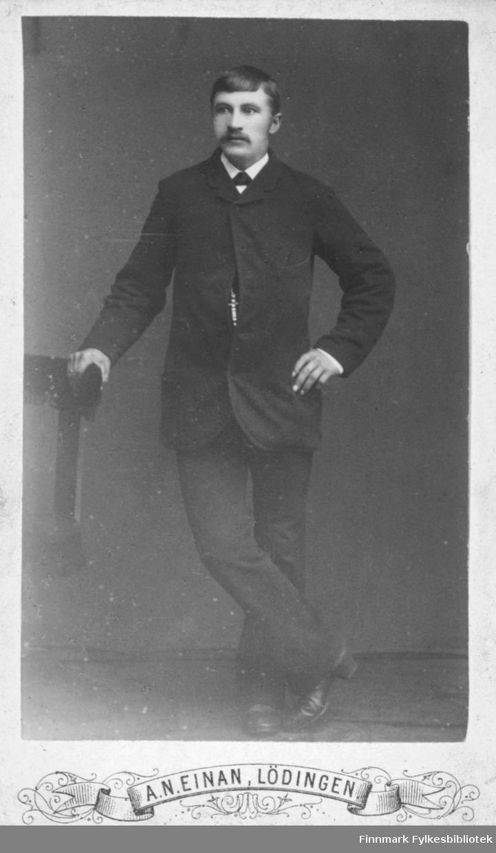 Helportrett av en mann. På bildet står han lent mot en stol. Han er kledt i mørk jakke og bukse. Han har hvit skjorte med slips eller halstørkle, og med en mørk knute i halsen. Han er fotografert i et atelier