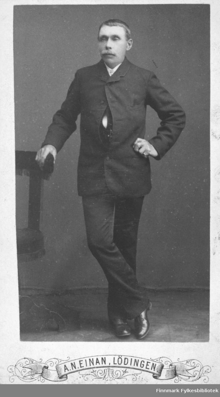 Portrett av ukjent mann med bart. Han er kledt i mørk jakke og bukse. På bildet står han og holder i en stol
