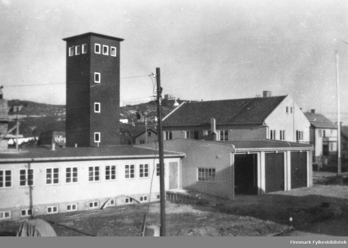 Fotografi av Vardø brannstasjon? På bildet ser man en lang bygning med mange vinduer bortetter langveggen. Den har et høyt tårn. Ved siden av står det en stor garasje med tre porter. Bak denne kan vi se flere bygninger som ser ut som boliger. Bortfor garasjen står det en flaggstang. Midt på bildet er det en lyktestolpe med kabler festet til