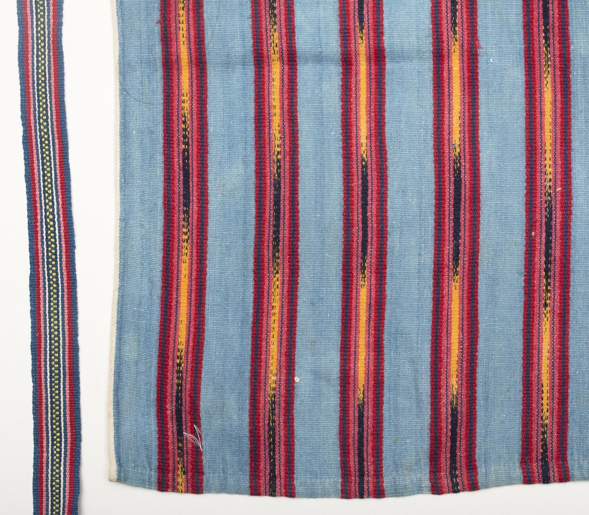 Midjeförkläde med ljusblå botten och breda jämt fördelade ränder i rött, gult och mörkblått, där de gula och mörkblå är flamgarnsfärgat. Ytterst längs långsidorna löper en smal vit kant som fortsätter på baksidan i den 4 mm breda sidfållen. Fåll nertill ca 10 mm. Linning av ett tyg liknande förklädets, bredd 15 mm, dubbelvikt över förklädeskanten. I sidorna är 1150 mm långa handvävda, mönstrade knytband fastsydda.
