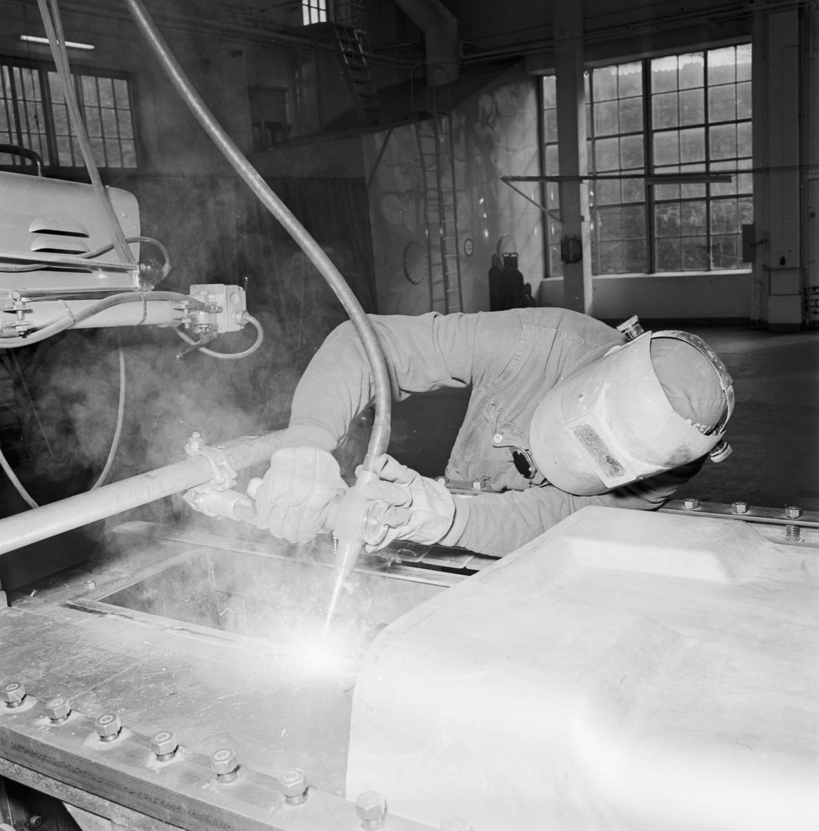 Övrigt: Foto datum: 16/3 1964 Verkstäder och personal. Bilder till reklambroschyr (Myllenberg) svetsning, dykare i arbete plåtpressen. Närmast identisk bild: V28534, ej skannad