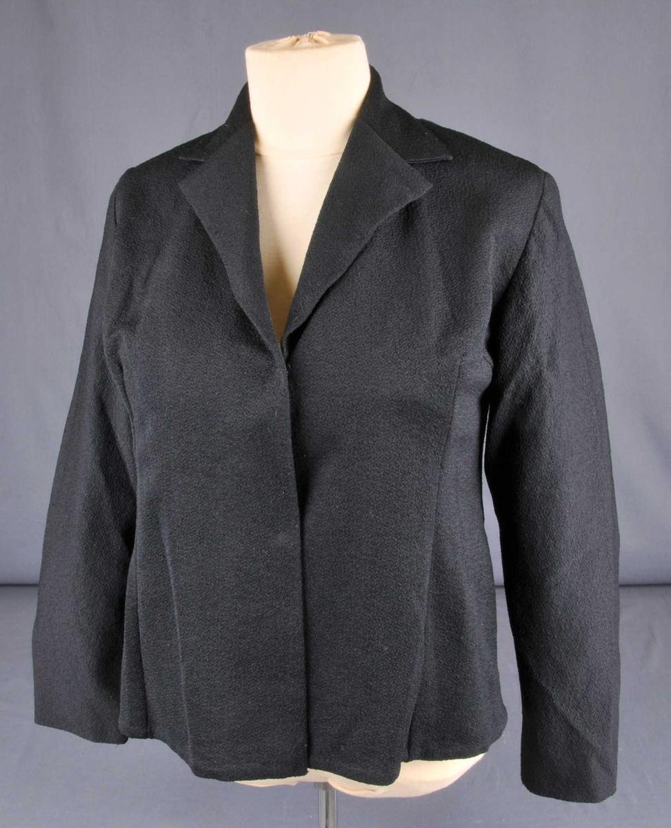 Jakke av svart tøy, er maskinsauma, med svart kunstfiber for, fest til jakka med håndsaum. Tosaums arm. Jakka er lett utsvinga med fire innsnitt framme og to bak ved nakken. Tri trykknappar framme.