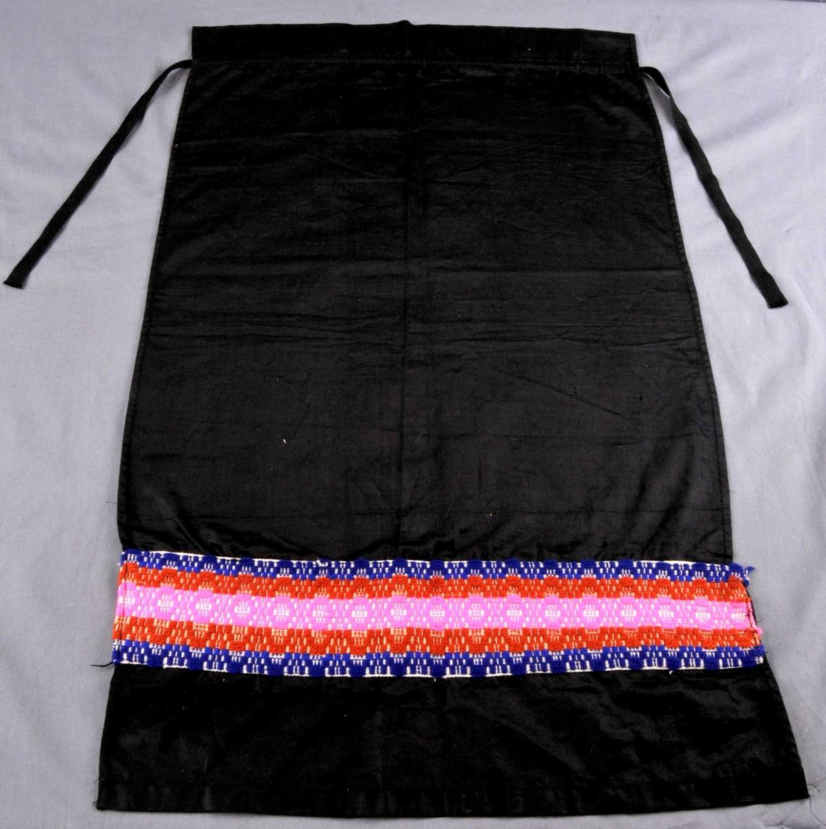 Forkle av svart lasting med ein løpegang for ein svart ullbendel som er nytta som knyteband. 5 cm rynkehovud i øvrekant. På eit 9 cm breit dekorfelt i tavlebragd. Forkle er sauma  med maskin.