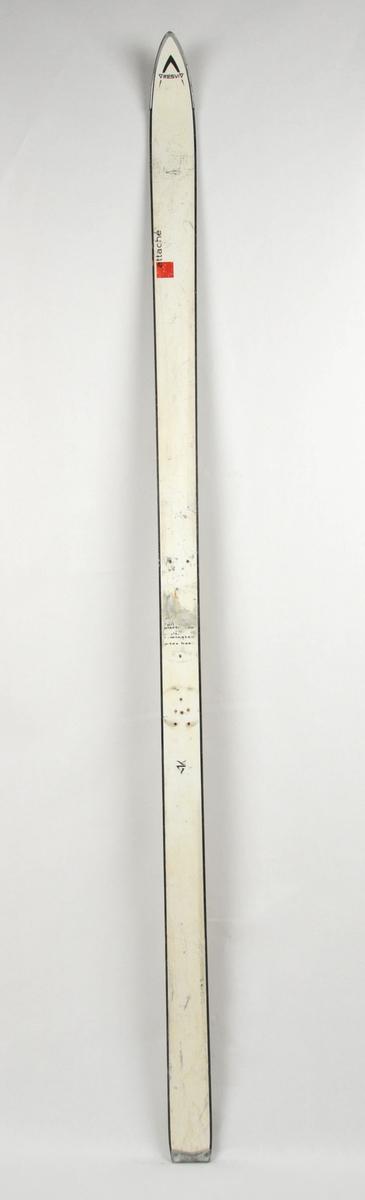 Alpinski av tre med såle av plast og topp av hardplast. Stålkant langs såla i form av ledd som er skruva på. Beslag på framtupp og baktupp. Kvit overside, gul såle. Det har vore bora hol til bindingar.